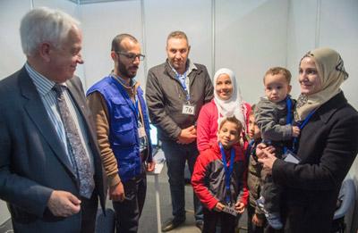 جان مک کالوم (چپ) در ملاقات با یک خانواده سوری در کمپ پناهندگان